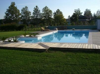 piscina immersa nel verde del giardino circostante curato e tagliato
